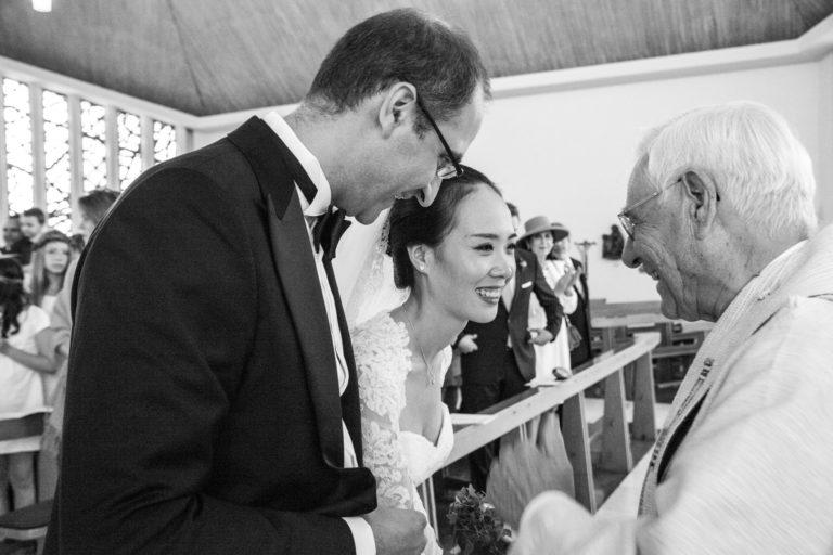 Hochzeitsreportage Kirche Freiburg Braut lächelt den Pfarer an