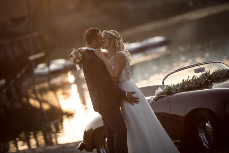 Hochzeitsfotograf_freiburg_basel_zuerich_portraitshooting_sonnenaufgang_paar_kuesst_auto_seepark